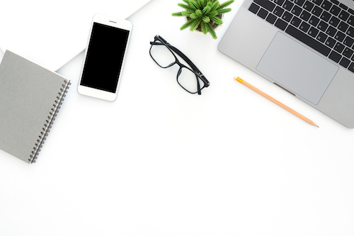 Creative flat lay photo of workspace desk. Top view office desk with laptop, glasses, phone, pencil, notebook and plant on white color background. Top view with copy space, flat lay photography.